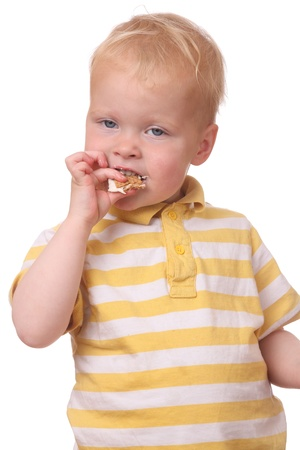 Portrait of a young kid eating cookies on white background photo