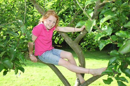 Smiling girl sitting in a tree photo