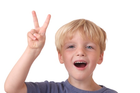 Winning boy shows victory sign on white background photo