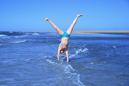 Young girl doing cartwheels on the beach photo