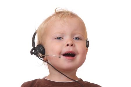 Niño divertido joven con auriculares sobre fondo blanco Foto de archivo