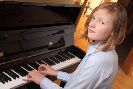 Young blond girl plays piano photo