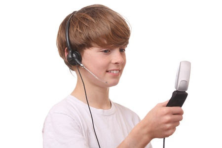 Young boy with cell phone and headset on white background photo