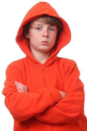 moody background: Young boy wearing an orange hoodie on white background Stock Photo