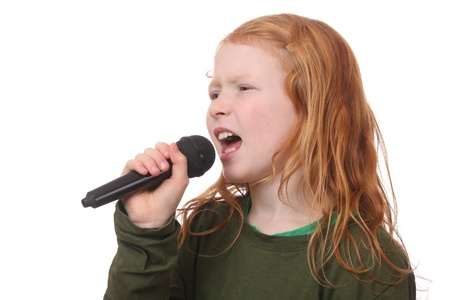 Young red haired girl singing into microphone on white background Stock Photo - 16690015
