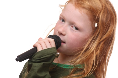 Young red haired girl with microphone on white background photo