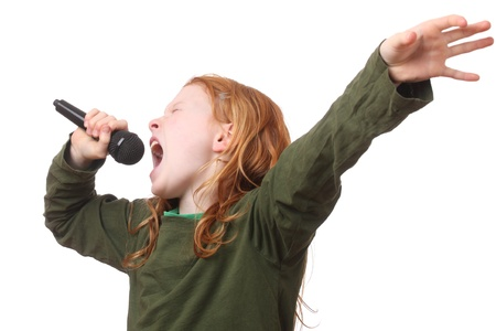 sing: Young red haired girl singing into microphone on white background Stock Photo