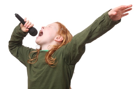 Young red haired girl singing into microphone on white background photo
