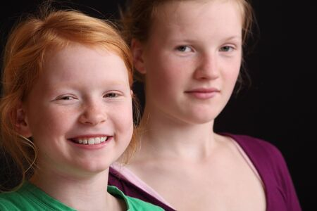 Two happy girls on black background Stock Photo - 16763201
