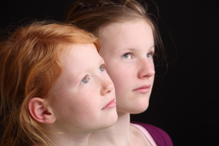Portrait of two cute looking girls on black background Stock Photo - 16763205