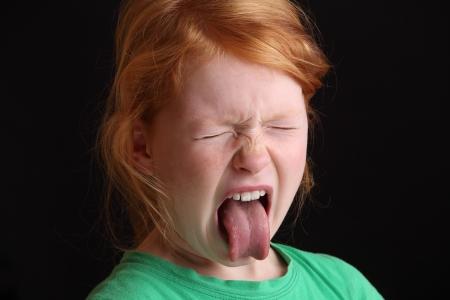 lengua afuera: Retrato de una chica joven enojado sacando la lengua Foto de archivo