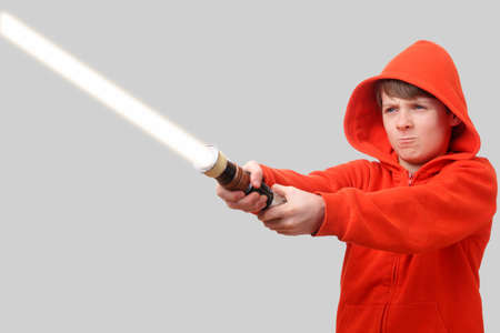 Young boy in hoodie holding a lightsaber