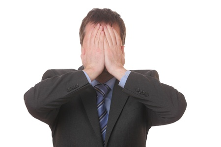 Stressed businessman covering his face with his hands on white background