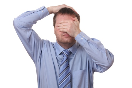 blunder: Stressed businessman covering his face with his hands on white background