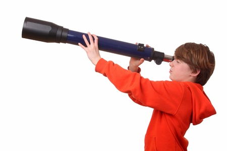 Young boy looks through a telescope on white background
