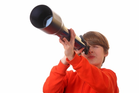 Young boy looks through a telescope on white background photo