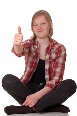 crosslegged: Young girl sitting cross-legged with thumbs up on white background
