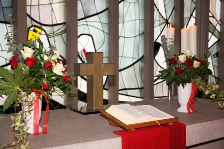 bible altar: Church altar with cross, flowers and bible Stock Photo