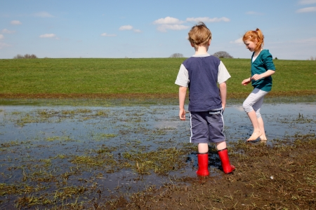 Two kids walking trough a muddy puddle photo