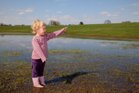 Happy toddler having fun in a muddy puddle photo