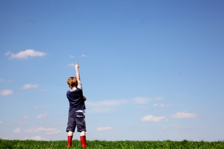 Boy in a meadow pointing to the sky photo