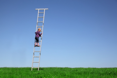 Young child climbs a ladder on a meadow with blue sky photo