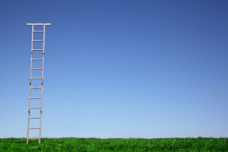 Ladder on a green meadow with blue sky photo