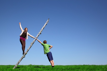 Young girl climbs a ladder on green meadow with blue sky photo