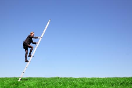 drabiny: Młoda businesswoman wspina się po drabinie na zielone łąki i błękitne niebo Zdjęcie Seryjne