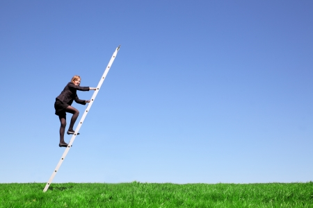 Young businesswoman climbs a ladder on green meadow and blue sky Stock Photo