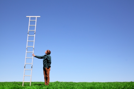 Young teenage boy holds a ladder on green meadow and blue sky photo