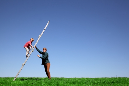 Young boy climbs a ladder on green meadow with blue sky photo