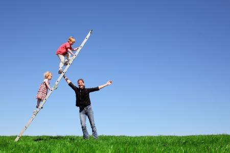 Familie plezier op groene weide en blauwe hemel