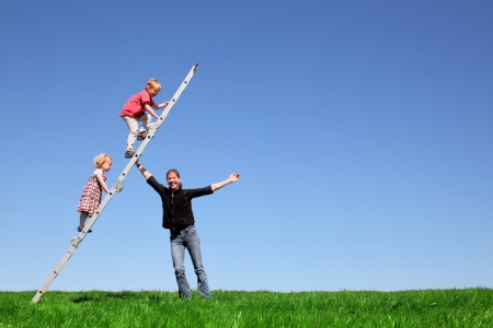 Family fun on green meadow and blue sky
