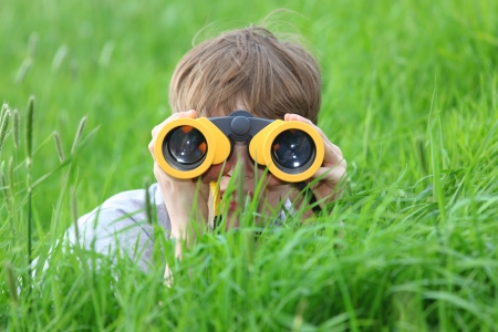 Young boy in a meadow looking through binoculars  photo