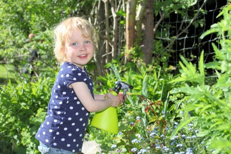 insecticidal: Happy child in garden sprays roses
