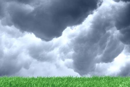 Dark grey clouds over green meadow photo