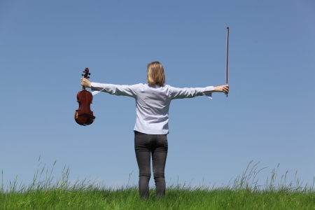 Teenage girl playing violin on meadow over blue sky  photo