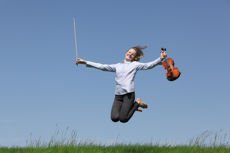 Teenage girl playing violin on meadow over blue sky
