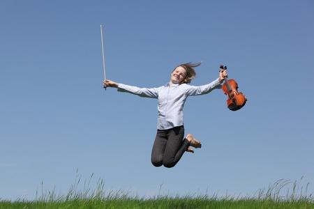 Teenage girl playing violin on meadow over blue sky