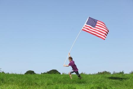 juventud: Chico joven patriótica marcha con una bandera americana en la pradera grenn