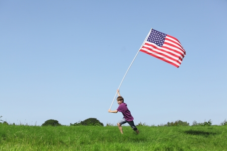 green flag: Patriotic young boy running with a american flag on grenn meadow