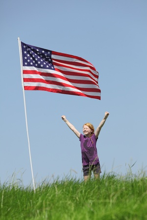 Patriotic young girl with american flag on green meadow photo