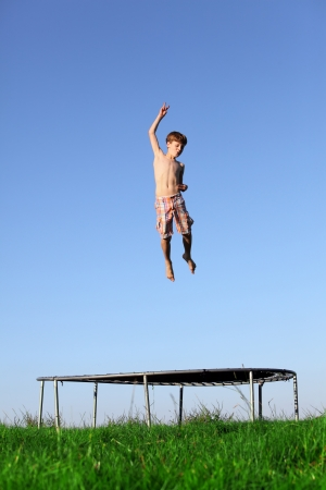 Young boy jumping on a trampoline on green meadow photo