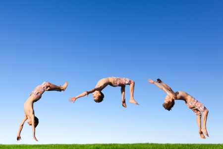 Young boy doing a backflip on a green meadow