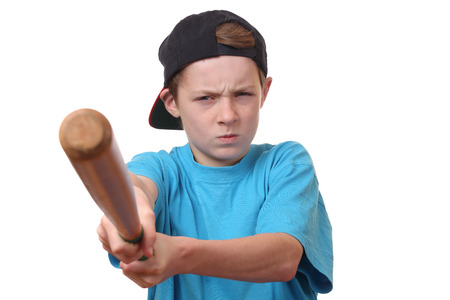 Portrait of an angry young boy holding a baseball bat on white background photo