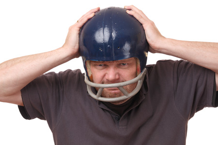 Portrait on an angry man wearing a football helmet on white background photo