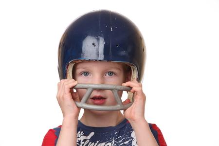 白い背景の上のフットボール用ヘルメットの少年の肖像画