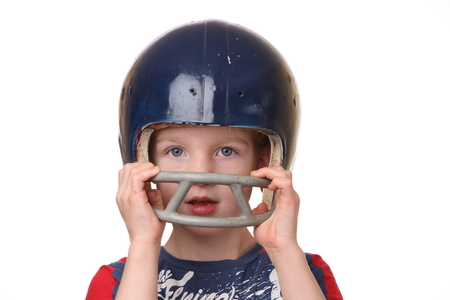 Portrait of a young boy with a football helmet on white background photo