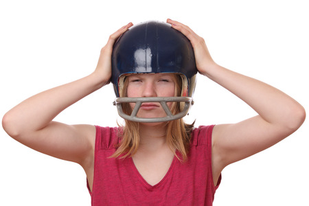 Portrait on an angry teenage girl wearing a football helmet on white background photo
